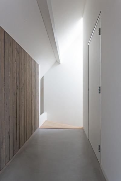 Overloop met stucwerk, betonvloer en houten wanden